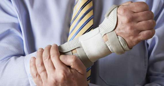 Close Up Of Businessman Suffering With Repetitive Strain Injury (RSI)